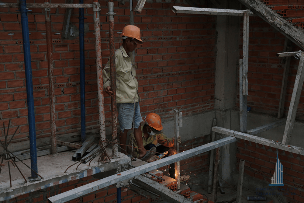 Thợ đang hàn sắt tạm để bắt thanh chắn an toàn công trình